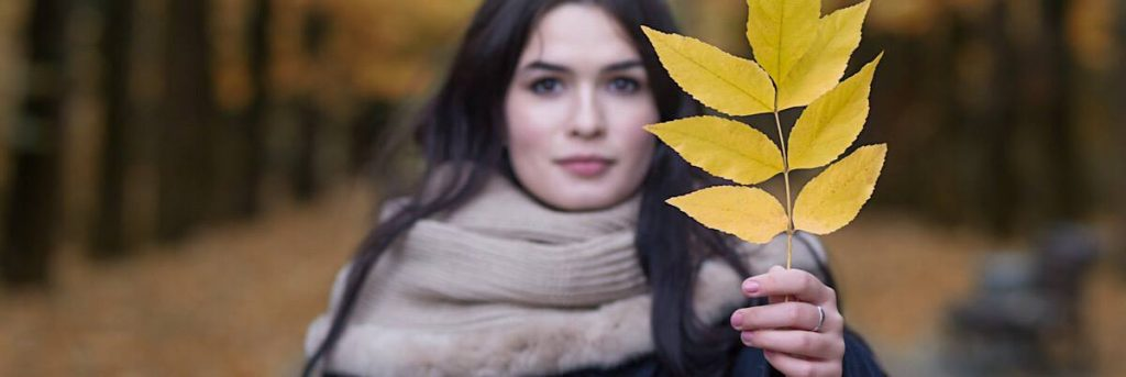 woman in woods holding leaf