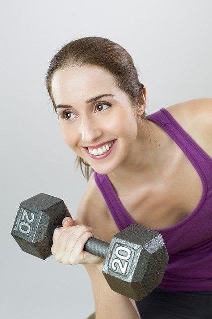 woman lifting dumbell in purple activewear