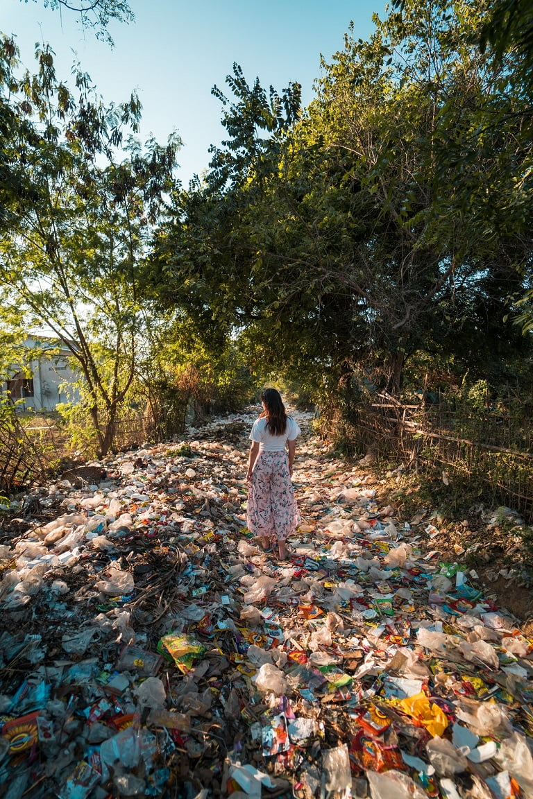 woman in country lane floored with plastic waste