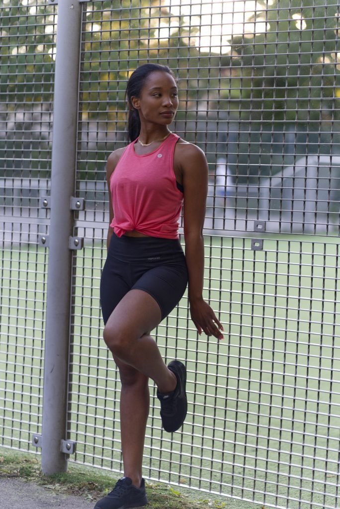 woman in lycell legging shorts leaning against fence