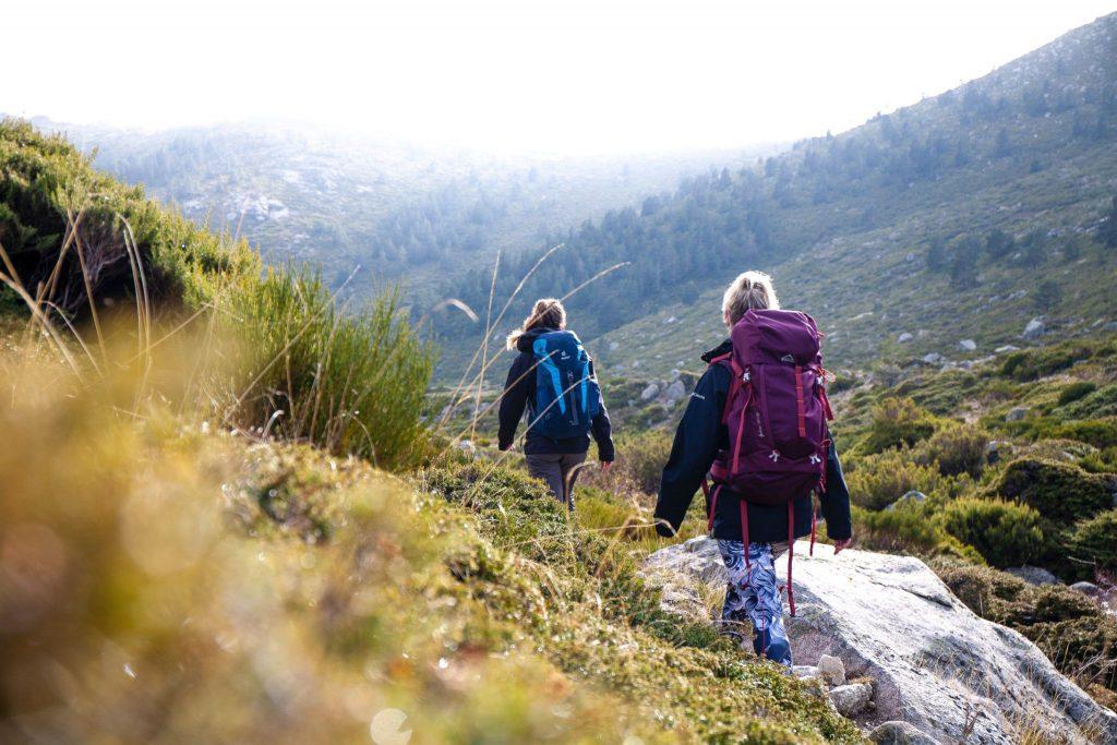 2 girls hiking through green hills