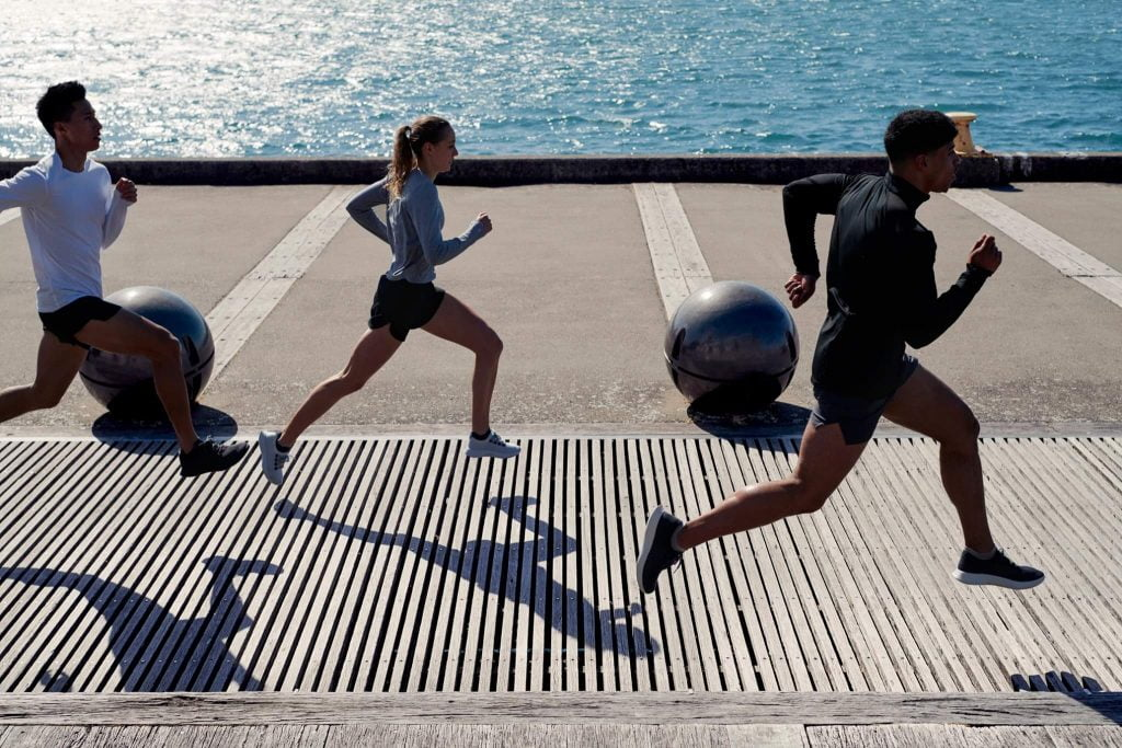People running on pier in sustainable shoes