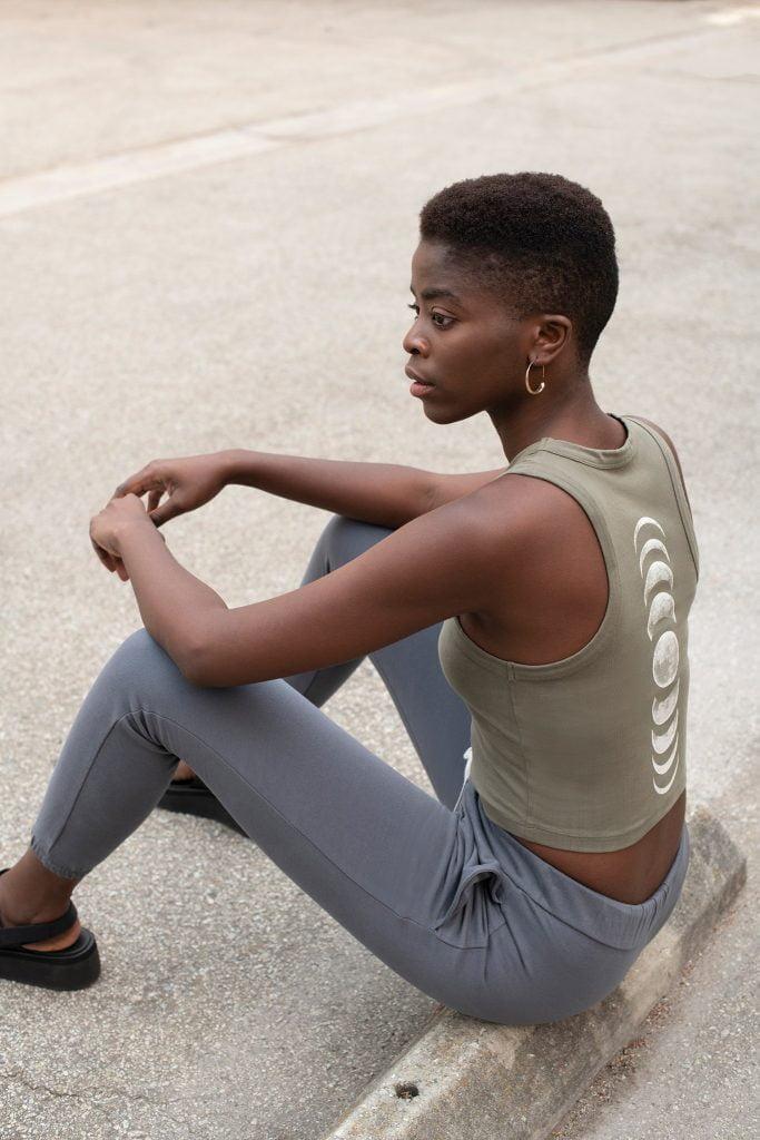 Girl in sportswear sitting in parking lot