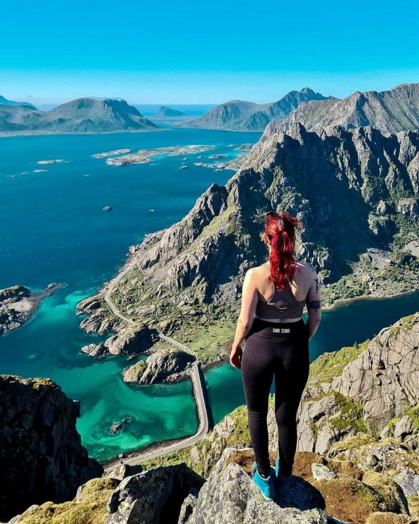 Girl in leggings on a mountaintop looking out over the sea