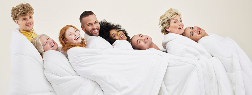 People wrapped up in duvets and laughing