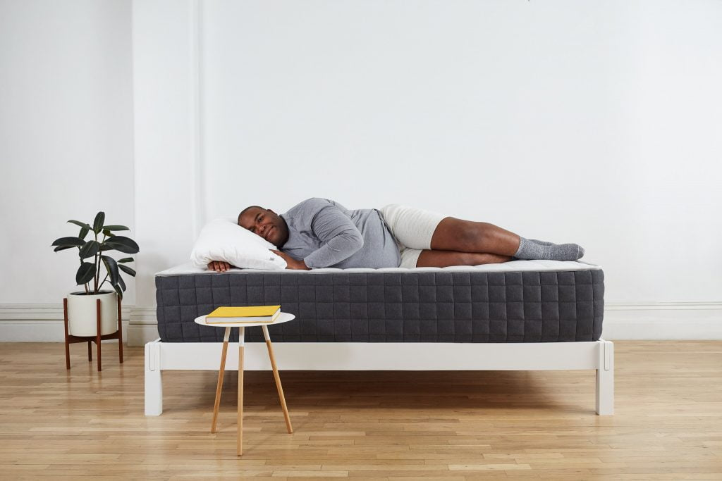 larger man lying comfortably on a mattress with designer furniture around