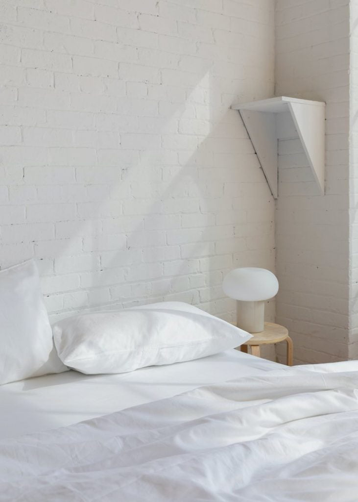 white brick wall behind white bed