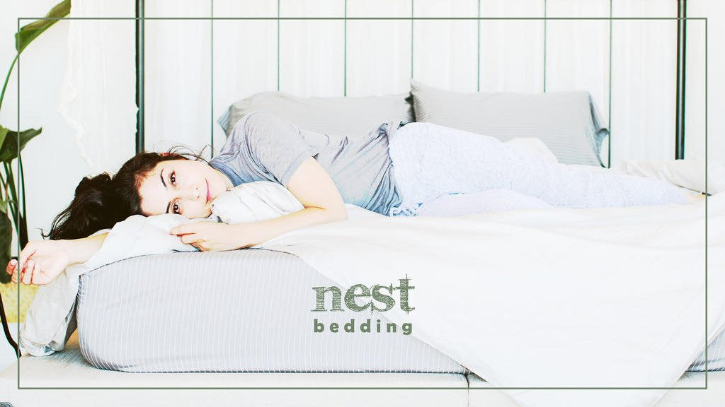 nest bedding, woman smiling in bed