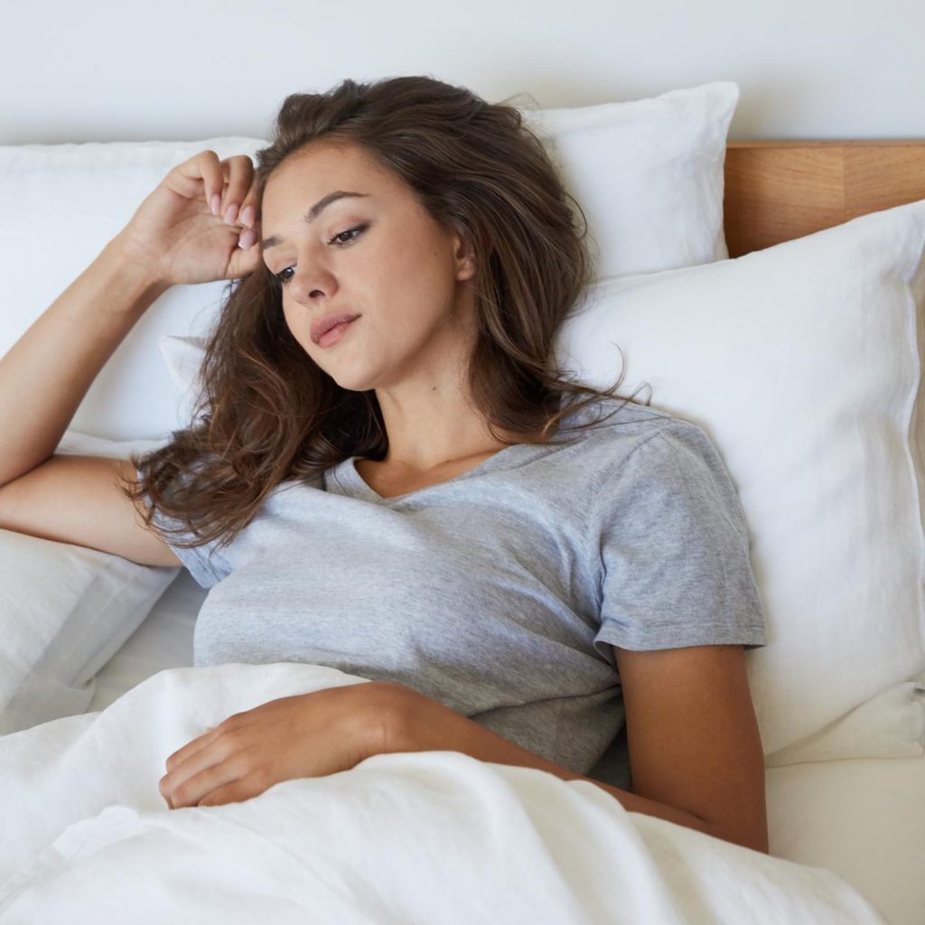woman thoughtful lying in bed