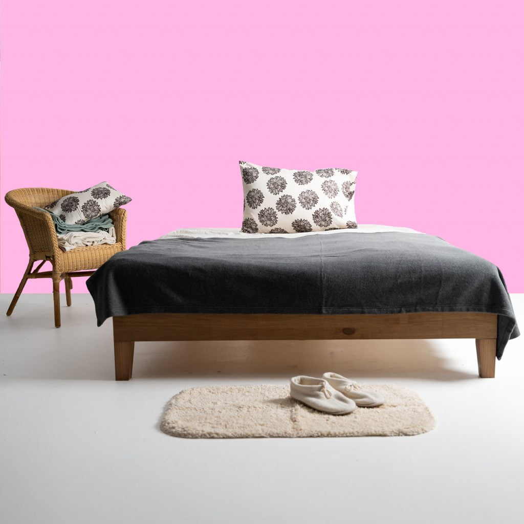 bed with pink wall behind