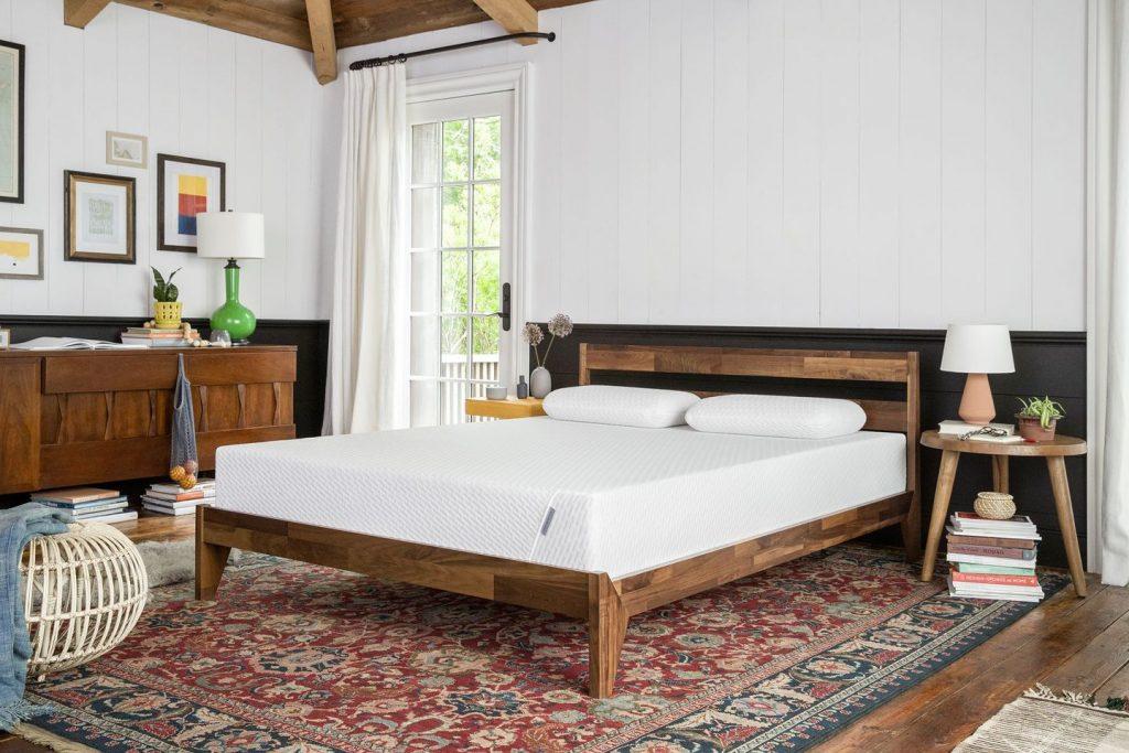 mattress on dark wooden bed frame over persian rug
