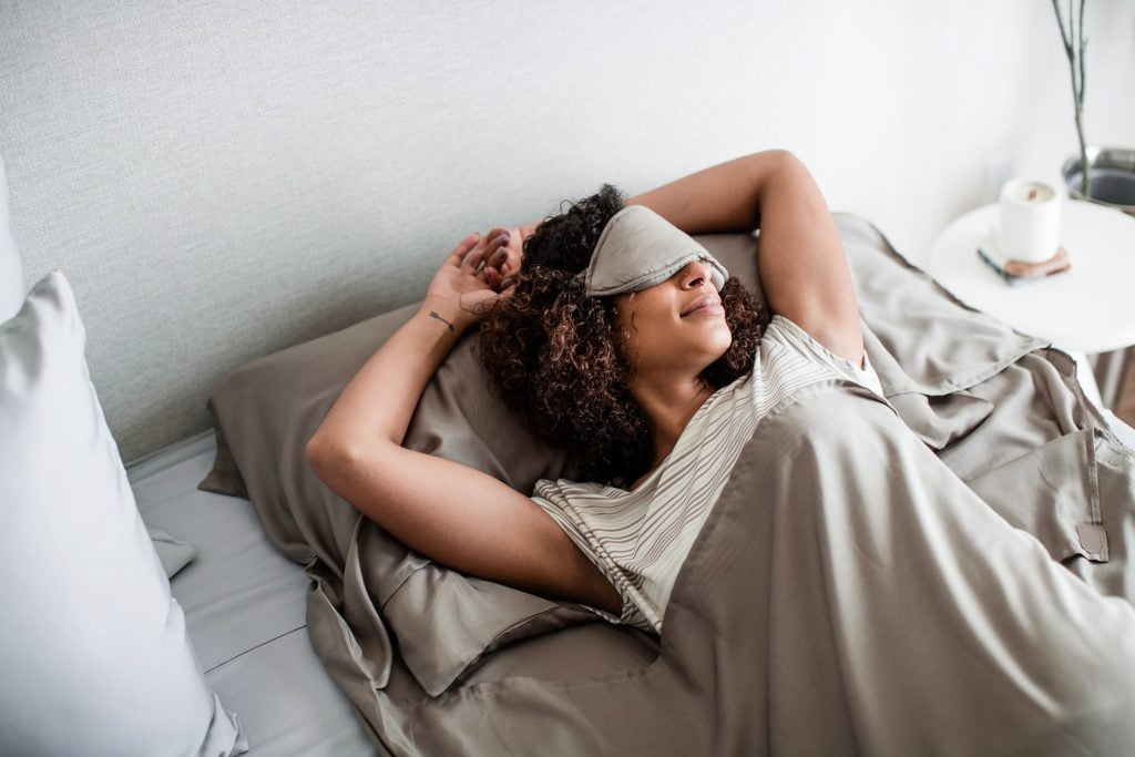 woman with eyes covered lying in bed